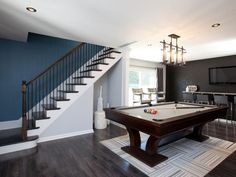 "AFTER: The ""couple's cave"" is the ultimate hang-out after the separating wall was removed and dark laminate flooring replaced old stained carpet. A modern light fixture connects the two spaces and looks posh over a custom pool table."