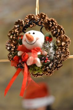 Snowman in a pine cone wreath Christmas decoration.