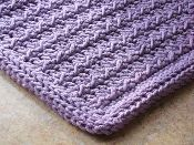 Use extra-thick Peaches 'n Creme cotton yarn and an absorbent crochet stitch pattern for a great bathmat or rug for the home. Crochet it while watching TV. Border looks like a real rug binding!