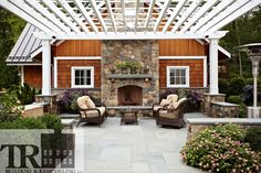Luxurious outdoor entertaining area with custom pergola and stone fireplace.