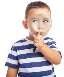 Kleiner Junge mit Lupe auf Schnitzeljagd