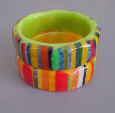 . SHULTZ bakelite multi-colored stripes bangles on a green  and a yellow base, 2-1/2  by1-1/8 by 1/3.            SHULTZ         and