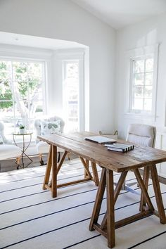 Lovely home office features a reclaimed wood sawhorse desk paired with an oatmeal linen rolling task chair placed atop a white rug with dark blue thin stripes.