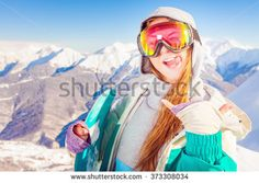 Snowboard. Female snowboarder on the background of high snow capped Alps in Swiss. Fun, cool girl