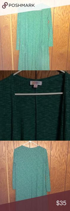 Small green LuLaRoe Sarah duster. Bought on posh. Lighter green than I was looking for. Thought it would match for Christmas but wasn't the right green. Worn few times. Heathered white pattern. If you need more pics let me know. 3rd pic is probably closest to its color. Just looking to get money back no profit. LuLaRoe Sweaters