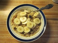 Healthy morning breakfast.  A bowl of oatmeal, a little brown unrefined sugar, a banana  and a bit of skim milk.
