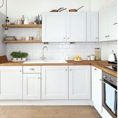 white kitchen, subway tiles, wood floor and worktops, some open shelving.