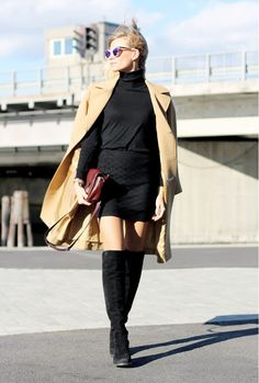 Tine Andrea wearing a turtleneck, vintage skirt, over-the-knee boots and a beige coat.