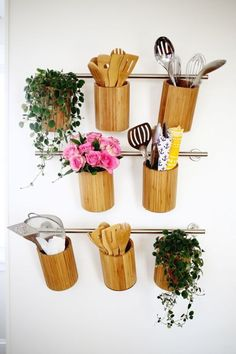 In lovely wooden canisters, a bevy of kitchen tools can stylishly hang beside potted plants and pretty floral arrangements.  See more at A Beautiful Mess »