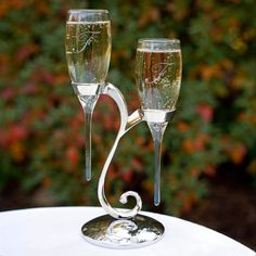 Our Raindrop Toasting Flutes with Swirl Stand are truly unique! These elegant wedding flutes feature a nickel-plated stand adorned with a sparkling rhinestone accent. The glass flutes fit right inside this one-of-a-kind stand -  perfect for holding your drinks when you want to head out to the dance floor!Size