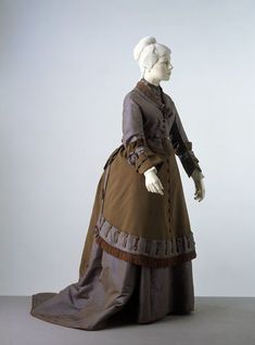 Dress Place of origin: UK (made) Date: 1868-1869 (made) Artist/Maker: unknown (production) Materials and Techniques: Silk and wool faced with silk, trimmed with silk fringe, lined with glazed cotton, reinforced with whalebone, machine and hand sewn Credit Line: Given by Miss E. Beard Museum number: T.6 to C-1937 Gallery location: In Storage