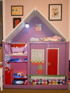 "A dollhouse from an old entertainment center.  I like how she kept the retractable doors so they can lpretend to ""open and close the house door"".  Caught my Fancy: Dollhouse Unveiled"