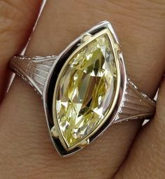 This beautiful example of the original 1920s engagement ring by  Belais Brothers (the finest and the first American jewelers to formulate  18K white gold ) that incorporates the gleaming precious metal with an  artistic grace and beauty that transcends specific Edwardian or Art Deco  style.   The main attraction of this dazzler is a bright old-cut  vintage Marquise** in Natural Light Yellow Color, VS2 clarity - EGL USA  CERTIFIED, although weighing in at 1.77ct , boasts the outer dimensions…