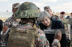 Theresa May, U.K. prime minister, looks at a model of a helicopter being held by a soldier at a Jordanian Army Base in Zarqqa, Jordan, on Monday, April 3, 2017. May began a visit to Jordan and Saudi Arabia on Monday, with the goal of building security and commercial ties. Photographer: Simon Dawson/Bloomberg via Getty Images