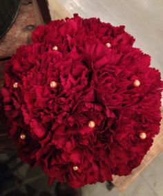 On a budget red bride bouquet! Texture galore with carnations and champagne pearls. #bridebouquet