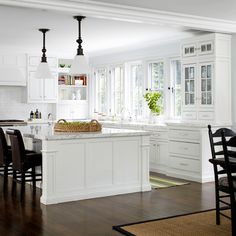 White cabinets with dark floors and like the dark chairs too.