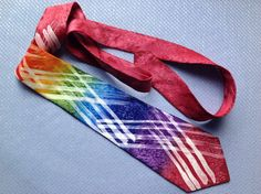 Rainbow batik diagonal Arty Stripe - Hand Painted Silk Tie / Necktie  wine, red, orange, yellow, green, sky blue, blue, purple marble pattern background  This tie was painted using the batik method to achieve the design.  Free postage within the UK - anywhere else the cost is to cover the postage.     A standard tie shape, 9cm wide and approximately 144cm long  If you would like the exact length please contact.  The silk used is a Matt crepe backed satin, which gives 'body' to the tie i.e…