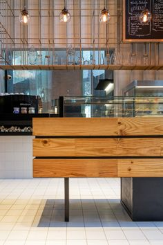 A cage-like grid of brass poles surrounds the upper section of this double-height patisserie.