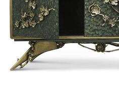 Spellbound Cabinet is a luxury design piece full of nature inspiration. The metal aged brass organic lace, in the shape of beautiful flowers and small charming lizards, makes this storage cabinet an unique design piece. An exotic design that is completed with a coating of peacock feathers, which are placed one by one for master artisans that apply all their technique to create luxury and unique design pieces.