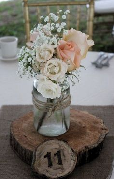 Tiffany peach roses, majolica spray roses and babies breath in a mason jar for a lovely summertime wedding. Tiffany peach roses, majolica spray roses and babies breath in a mason jar for a lovely summertime wedding. Mason Jar Centerpieces, Rustic Wedding Centerpieces, Wedding Table Decorations, Wedding Table Numbers, Mason Jar Flower Arrangements, Floral Centerpieces, Wooden Table Numbers, Mason Jar Flowers, Flower Jars