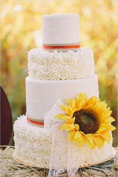 Sunflower wedding cake on hay bale. Cake Design: The Cakery --- http://www.weddingchicks.com/2014/06/04/country-burlap-and-lace-wedding/