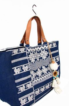 STAR MELA. Leila Em Bag.  Large navy tote bag with ecru cross-stitch embroidery. Leather handles. Striped cotton lining and large embellished tassle. Colour - Navy - Ecru. 100% Jute.  Grande tote bag navy con ricamo a punto croce. Manici in pelle. Fodera in cotone a righe. Colore - Navy/Ecru. 100% iuta.  € 110.00  #starmela #handbags #bags #summer #iute #cotton #beach #borse #estate #cotone #iuta #spiaggia #montorsigiorgiomodena #montorsimodenaeshop
