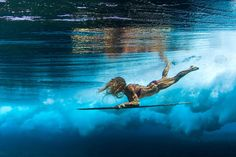beneath the waves | Female surfers beneath the waves - Yahoo! News | Donica Shouse duck diving a wooden alaia surf board.