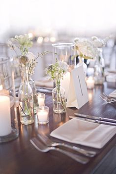 natural wedding decor with flowers in bottles.. this looks like it might be a…