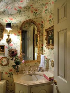 the wallpaper is a bold choice, but I love some of the elements, the mirrors, lamp, vanity all very warm.