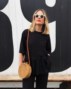 All black outfit with white sunnies and straw handbag