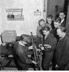 "Weapon Instruction to resistance fighters in the attic at Proost en Brandt, Russia 24-26 street, Amsterdam. This was a ""full service"" workshop for repairing small arms and helping with all other ordnance needs of the Dutch resistance. The rifle being demonstrated is the British Short Magazine Lee-Enfield Mk I. Sten SMGs can be seen on the repair bench."