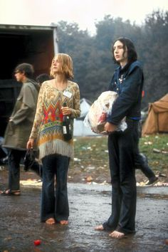 Hippie couple standing barefoot on a road holding a bundle & wine bottle during the Woodstock Music & Art Fair.