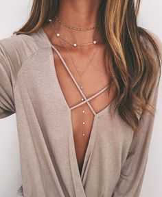 Love the layered long drop necklace with the beige sweater crisscross neck line//