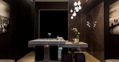 A ideia do arquiteto René Fernandes ao idealizar este banheiro todo na cor preta era destacar as peças como joias. Com 12 m², o espaço é dividido em setores pelo totem revestido por espelhos. Repare que a base da bancada é assimétrica e segue o tom piso, mas sobressai frente ao todo. A cuba de apoio e o misturador de mesa são da linha Slim, da Deca. A iluminação trabalhada é da La Lampe