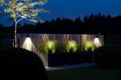Project 'In de Wolken.' van Heart for Gardens. Verlichting, siergrassen, bloembakken, schutting.