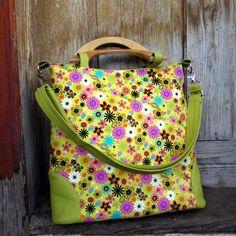 Klára rozkvetlá kabelka,kabela,taška pro všestranné využití do práce,do školy na výlet ušitá z krásné bavlněné látka se vzorem kytiček,různě barevných spodní oválný díl a všité spodní díly i zadní díl jsou ze krásně zelené koženky taška má jednoduchý tvar vyztužená ronarem zipové zapínání tašku zdobí dřevěná ucha vyrobena v malé truhlářské ...