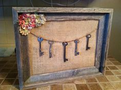 Empty frame, burlap, twine and old skeleton keys.  Embellished with paper flowers.:)