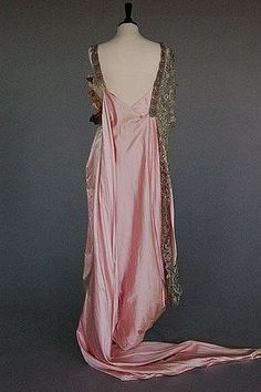 """Dress, back view.  Jean-Philippe Worth, 1913-1914.  """"Worth ball gown the label numbered for 1902 but construction circa 1913-18    the woven signature label stamped 57821 and applied to broad petersham waistband, with elaborate beaded and paste inset palmette which meanders from right shoulder to left front, broad silver bobbin lace trim, separate chiffon lace edged inner skirt, pointed train with arm-loop for dancing, bust 92cm, 36in.  Kerry Taylor Auctions."""""""