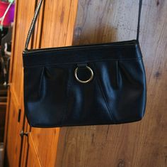 Vintage black bag with goldish metal ring A beautiful vintage bag with a gold metal ring in the front. Long handle, which you can put inside the bag to turn into a clutch. Two inner parts as pockets. Great for a lot of occasions. Vintage Bags