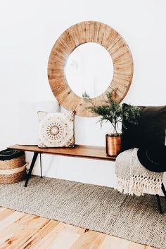 a simple boho entryway with a wooden bench, a woven rug, a basket, a wood clad mirror and pillows