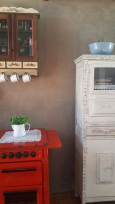 Cantinho de casa. Fogão antigo canecas esmaltadas e armários em estilo colonial.