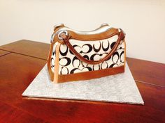 Coach Purse Cake. Gluten free chocolate fudge cake, vanilla buttercream, and marshmallow fondant details.