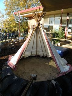 TeePee sand box from bamboo poles lodged in a tractor tire, tied together at the top, then draped with a sheet or canvas material. How fun! My nephews would love this! from Irresistible Ideas for Play Based Learning.