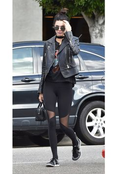Kendall Jenner wears mesh detail leggings, a graphic tee, moto jacket, a choker, and topknot
