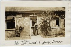 "Photograph of Gavin Green holding his cat in front of his store ""Yea Old Curiosity Shop"" on Hamilton Street in Goderich, Ontario. ""66"" is written in several places on the front. The back reads: "" We, the cat and I turning key in door of Old Curiosity Shop for last time.  May 30, 1948   GH Green"". The curiosity shop had been a fixture of the Goderich downtown since 1902. Huron County, Back Read, Curiosity Shop, Museum Collection, Ontario, Hamilton, Turning, Photograph, Kitty"