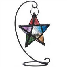 """NEW ITEM TO ECLECTIC ARTISANS!!! Suspended from a slender curlicue of wrought iron, a multicolored Pentagram casts a halo of elemental splendor! A unique & sacred shaped tabletop candle lamp that enlivens your next gathering with a festive glow. Perfect for any altar, sacred space or garden! Weight 1.4 lbs. Tealight candle not included. Lantern: 7 1/2"""" x 2"""" x 8"""" high; stand: 14"""" high. Iron, Glass.    7 1/2"""" x 2"""" x 14"""" high."""