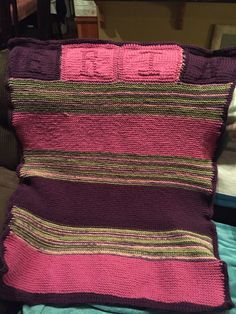 Knitted blanket for Erin. Used Loops and Threads Charisma. 3 skeins each of bouquet, fuchsia, and dark purple. Each letter knitted in a separate square which were then stitched together. Broad strips of color done in garter stitch. Three rows of single crochet for edging. 100% acrylic. Machine washable and dryable.