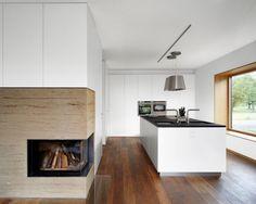 cuisine claire avec îlot central, hotte aspirante en acier et appareils électroménagers encastrables