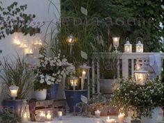 Biały balkon wieczorem: bugenwilla, kącicierń (Bougainvillea), psianka (Solanum rantonnetii 'Alba'), petunie (Petunia), Spartina, Pennisetum 'Hameln' , miskant (Miscanthus 'Zebrinus'). Zapalone świeczki, lampiony, lampki, świeczniki , Dekoracje Stoł