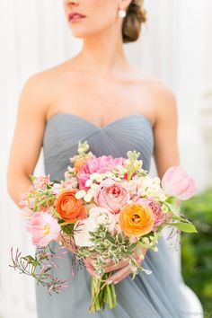 bridesmaid in an elegant strapless slate gown holds a loose bouquet of spring flowers including coral charm peony, romantic antique garden rose, caramel antique garden rose, peach stock, pink fringe tulip, peach ranunculus, white majolik spray rose, white button chamomile, variegated italian pittosporum& jasmine vine wrapped in cream satin ribbon.